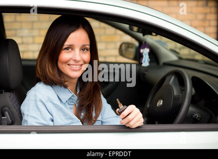 young woman looking out of her car window holding her keys. - Stock Photo