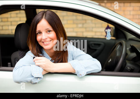 young woman looking out of her car window holding her keys - Stock Photo