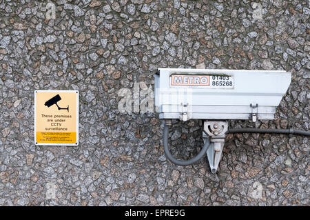 A CCTV security camera mounted on a wall. - Stock Photo