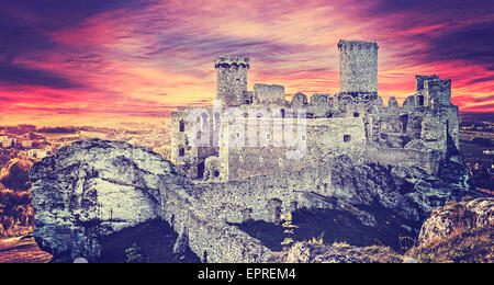 Vintage toned picture of a dramatic sunset over Ogrodzieniec castle ruins, Poland. - Stock Photo