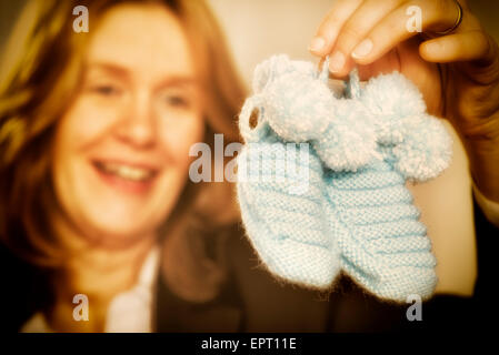 Blond woman is holding two blue baby shoes - Stock Photo