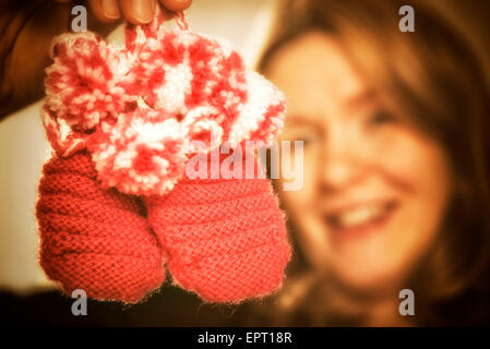 Blond woman is holding two pink baby shoes - Stock Photo
