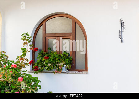 Rounded wood frame  window with red geraniums flower pots and black iron thermometer on white wall - Stock Photo