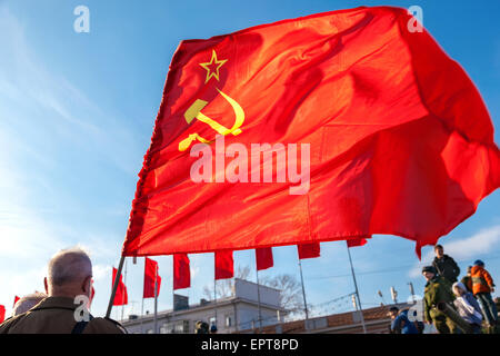 Red flag waving over blue sky background at the Kuibyshev square in sunny day - Stock Photo