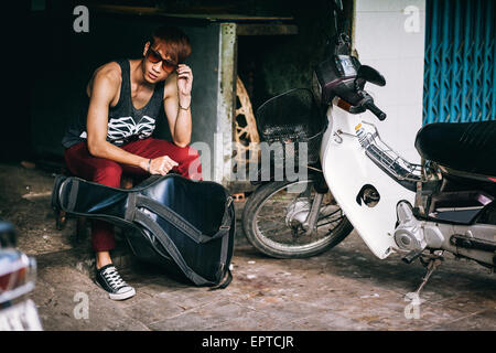 69fb15a19e ... asian fashion street teenager in style sunglasses with guitar case and  motorbike - Stock Photo