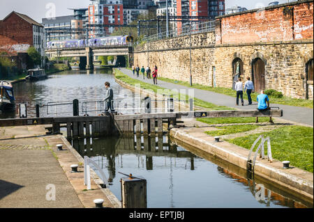 Man Sitting on Lock Gates Leeds and Liverpool Canal,Leeds,West Yorkshire - Stock Photo
