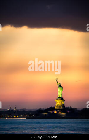 Statue of Liberty under a dramatic sunset light as viewed from Brooklyn, New York - Stock Photo