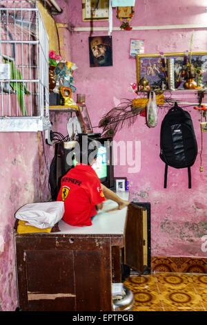 Mumbai India Asian Dharavi Kumbhar Wada slum high population density poverty low income poor resident boy home watching - Stock Photo