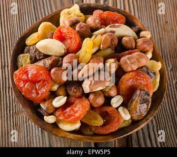 Healthy Mix nuts and dried  fruits on wooden background. - Stock Photo