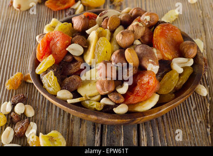 Nuts and dried  fruits on a wooden background. - Stock Photo