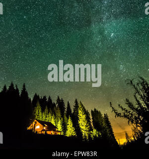 Alone house in night lights with stars, deep sky and milky way on mountainbackground - Stock Photo
