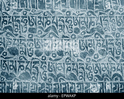 Buddhist mantra carved in stone as background - Stock Photo
