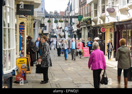 Tourists visiting and shopping in York's popular Stonegate shopping street. In York, England - Stock Photo