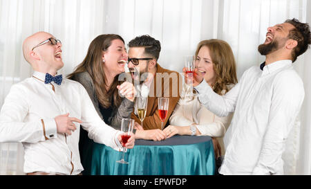 Friends laughing hilarious in a bar, holding glasses of wine - Stock Photo