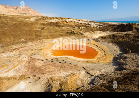Sinkhole or open pit with orange salty water on the shore's of the dead sea at the end of the summer when the water - Stock Photo