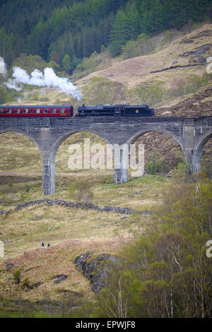 The Fort William To Mallaig Steam Train passing over the railway viaduct at Glenfinnan in Scotland - Stock Photo