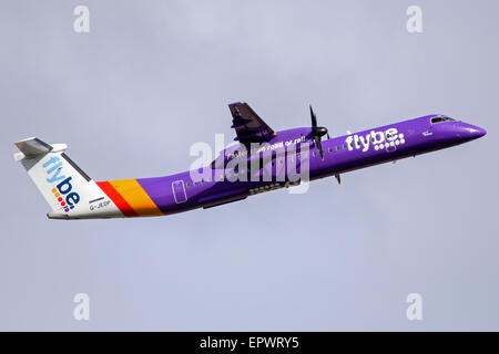 FlyBe DeHavilland Dash-8 climbs away from runway 05L at Manchester airport. - Stock Photo