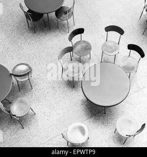 Round tables and chairs stand in empty cafe interior top view