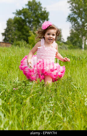 cheerful girl in a pink dress runs on a grass - Stock Photo