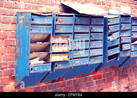 broken mailboxes on an old brick wall - Stock Photo