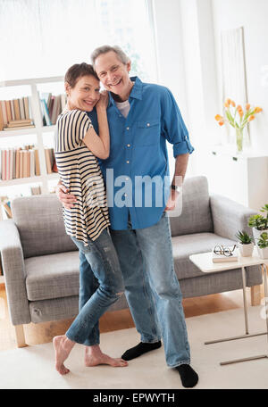 Senior couple embracing in living room - Stock Photo