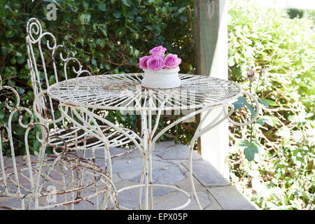 White wrought iron outdoor table and chairs on patio with vase of pink roses in South African home - Stock Photo