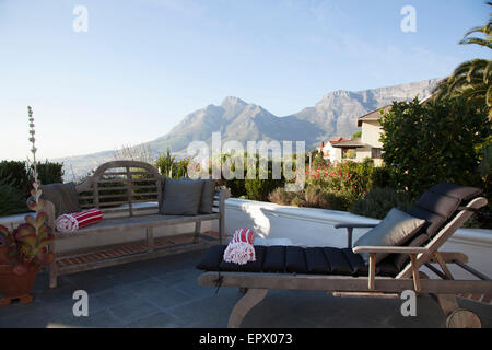 Wooden bench and lounger on patio with views of Table Mountain, South Africa - Stock Photo