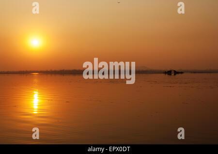 Sunset over Dal Lake, Jammu and Kashmir, Srinagar. Orange tones and mountain in the background. - Stock Photo