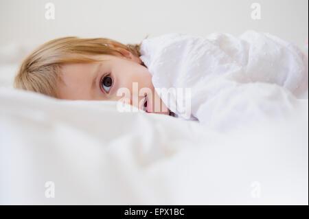 Girl (2-3) lying on bed - Stock Photo