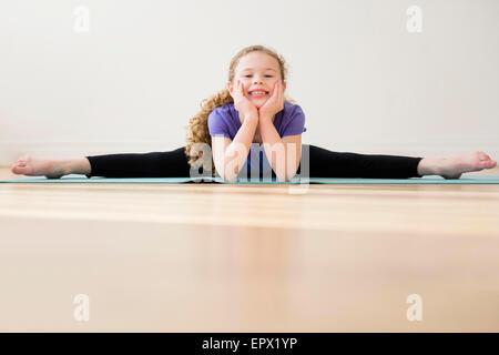 Girl (10-11) doing splits - Stock Photo