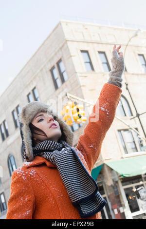 USA, New York, Brooklyn, Woman calling taxi in winter - Stock Photo