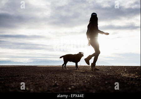 USA, Colorado, Woman walking with dog at sunrise - Stock Photo