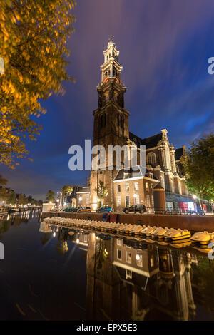 Netherlands, North Holland, Amsterdam, Illuminated Westerkerk Church reflecting in still canal - Stock Photo