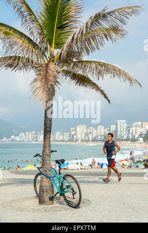 RIO DE JANEIRO, BRAZIL - MARCH 22, 2015: Jogger passes a bicycle locked to a palm tree on the boardwalk at Arpoador near Ipanema