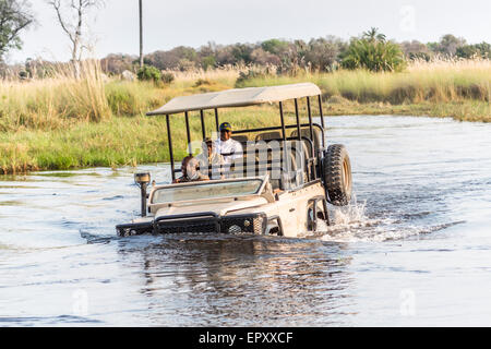 Safari jeep with driver and tourists laughing and having fun, fording a deep river in the Okavango Delta, Botswana