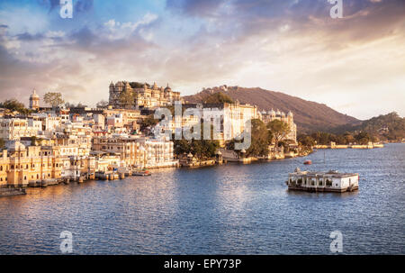 Lake Pichola with City Palace view at cloudy sunset sky in Udaipur, Rajasthan, India - Stock Photo