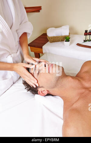 Hands of masseur touching head of man while giving massage in spa - Stock Photo