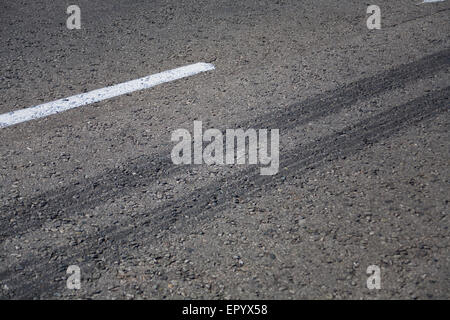 Close up view of rubber tyre tracks on a tar road from vehicles braking harshly - Stock Photo