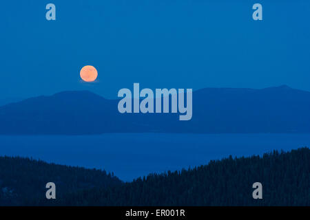 Full moon rising over lake Tahoe as seen from Squaw Valley high camp. - Stock Photo