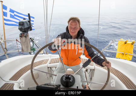 Young skipper drives the sailboat in the open sea. Yachting. Sailing. - Stock Photo