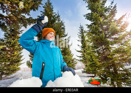 Happy boy ready to throw snowball in forest