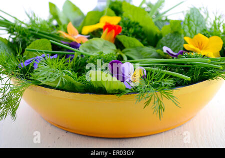 Cooking with herbs concept with fresh herbs and edible flowers in modern yellow fry pan skillet on white wood table. - Stock Photo