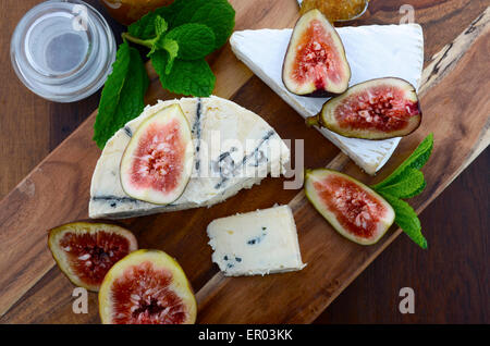 Fresh figs on wooden cutting chopping board with jar of fig jelly preserve and gourmet cheese on dark wood rustic - Stock Photo