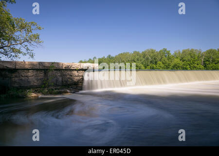 Long exposure of silky water pouring over man made dam in black and white - Stock Photo
