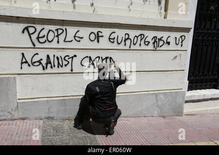 Athens, Greece. 23rd May, 2015. A protesters burns paints a graffiti on a wall near the German Embassy that reads - Stock Photo
