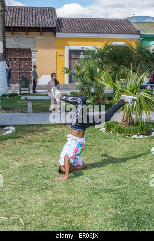 Teenage boy doing a headstand in a park in Antigua Guatemala - Stock Photo