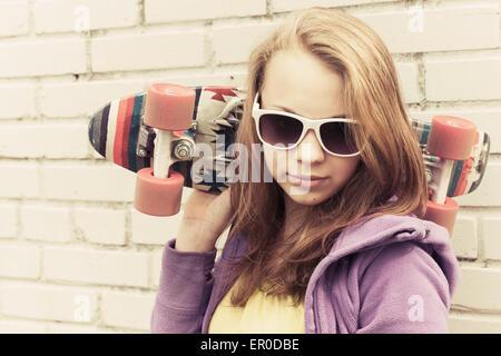 Blond teenage girl in sunglasses holds skateboard near gray urban brick wall, vintage tonal correction, old style - Stock Photo