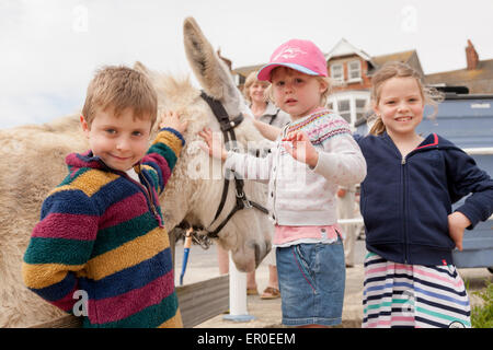 Donkeys on the beach with very young children, Weymouth, Dorset UK - Stock Photo