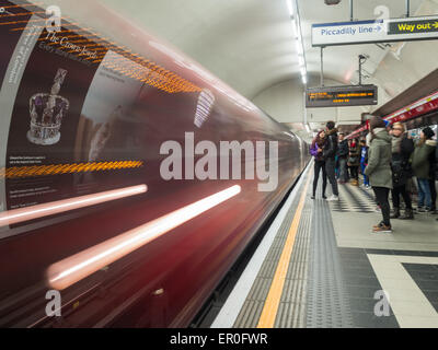Moving train at a London underground station with people - Stock Photo