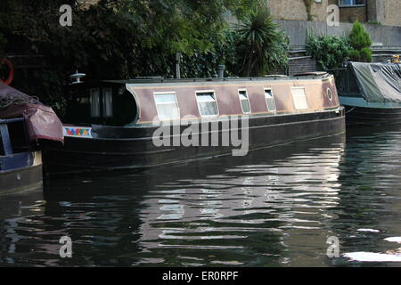 canal barge on canal river in Regents park London with bridge over - Stock Photo
